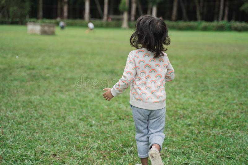 Girl running on the park. Back shot of a girl running on the park royalty free stock photos