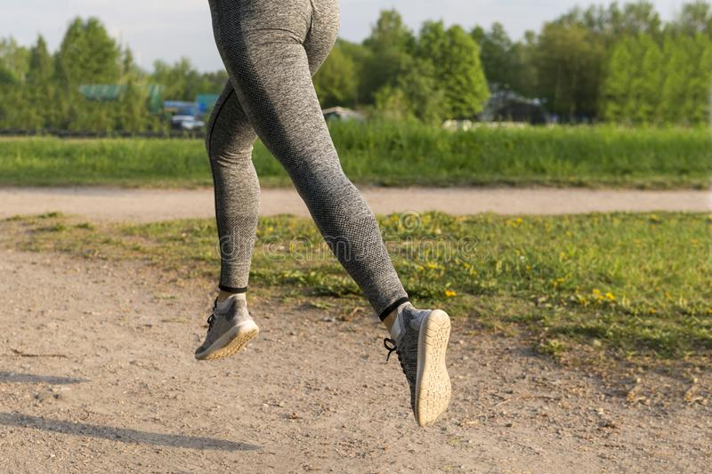 Girl running in the Park, women`s feet in gray leggings and sneakers on the path in the Park in the sun, runner stock images