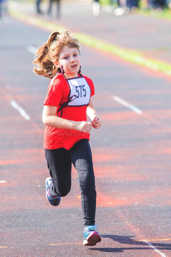 Girl running during a race. A girl running during a race stock photo