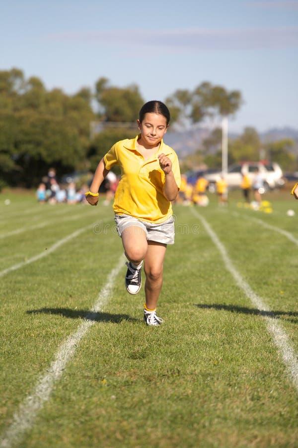 Girl running in race. Girl running in school sports race royalty free stock photos