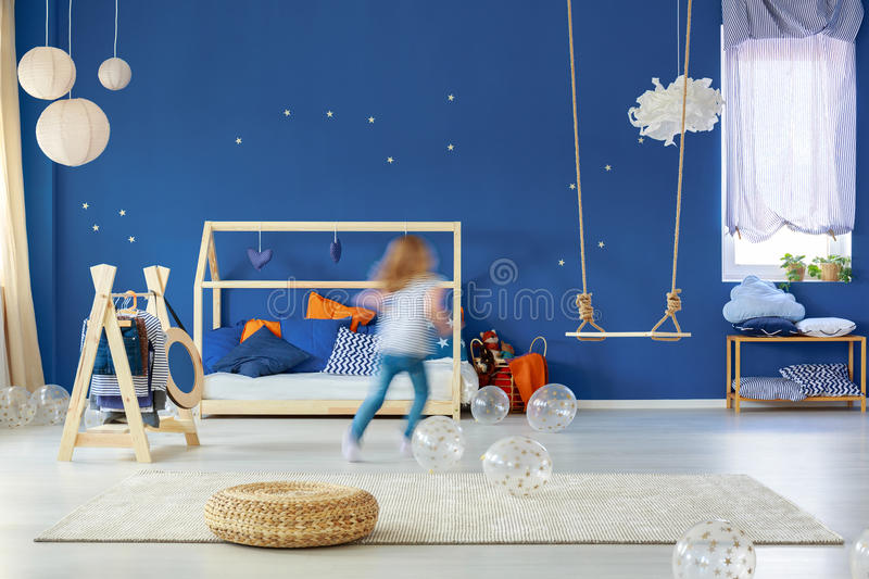 Girl running in room. Young girl running in blue stylish decorated room stock image