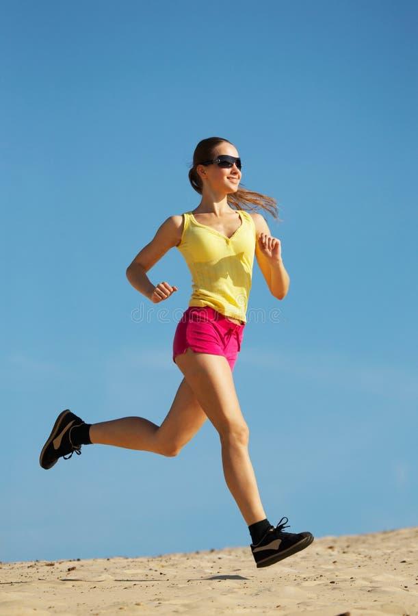 Girl running on sand stock photo