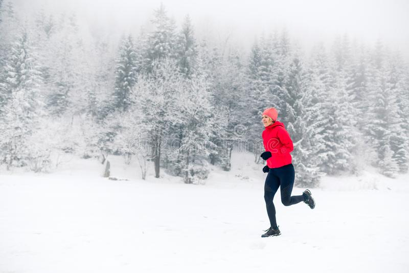 Girl running on snow in winter mountains. Sport, fitness inspiration and motivation. Young happy woman trail running in mountains. On snow, winter day. Female stock image