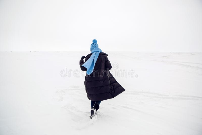 Girl running in a snowy field in a jacket stock photos