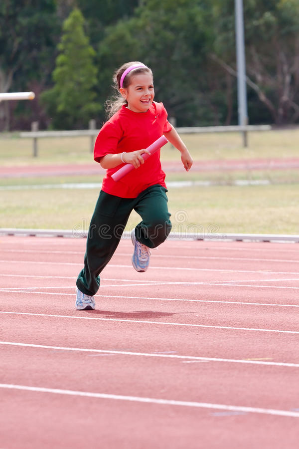 Girl running in sports race. A young girl running in a sports race at school stock photography