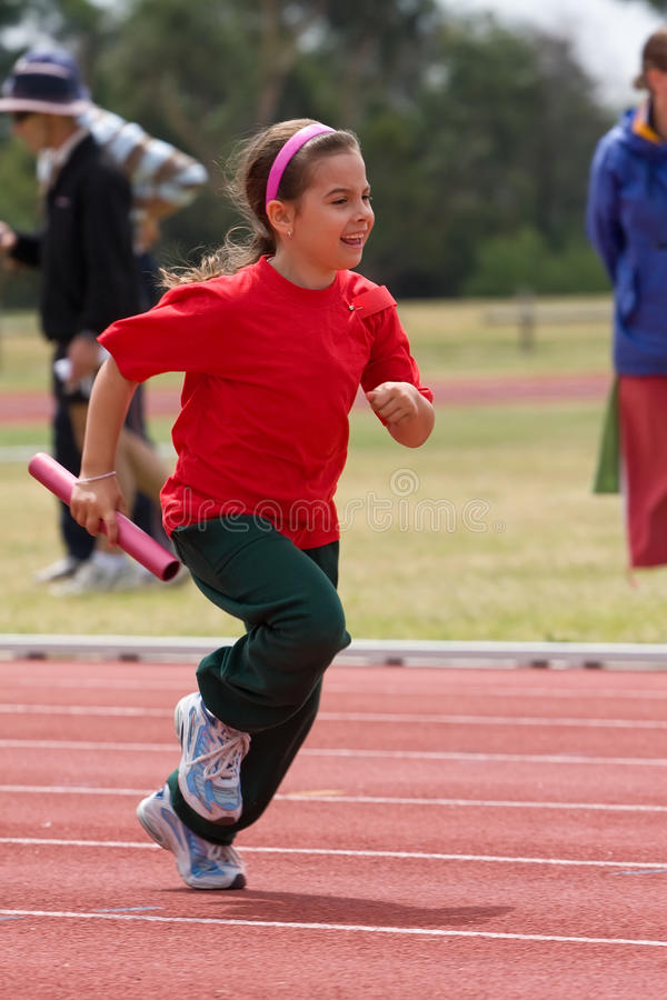 Girl running in sports race. A young girl running in a sports race at school stock photos