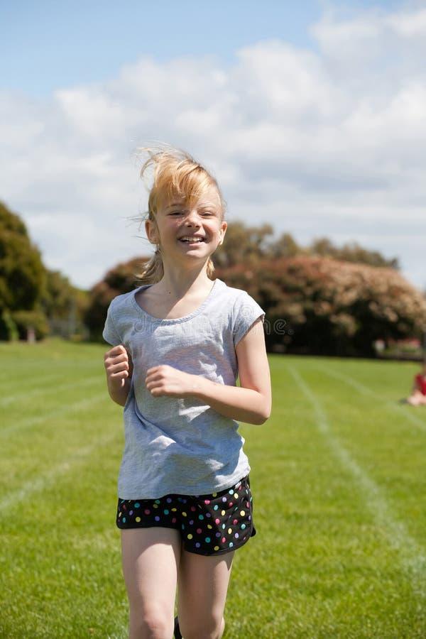Girl running in sports race. stock photo
