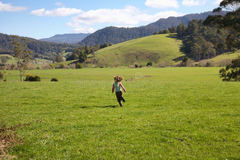 Girl running in Tasmanian farmland royalty free stock images