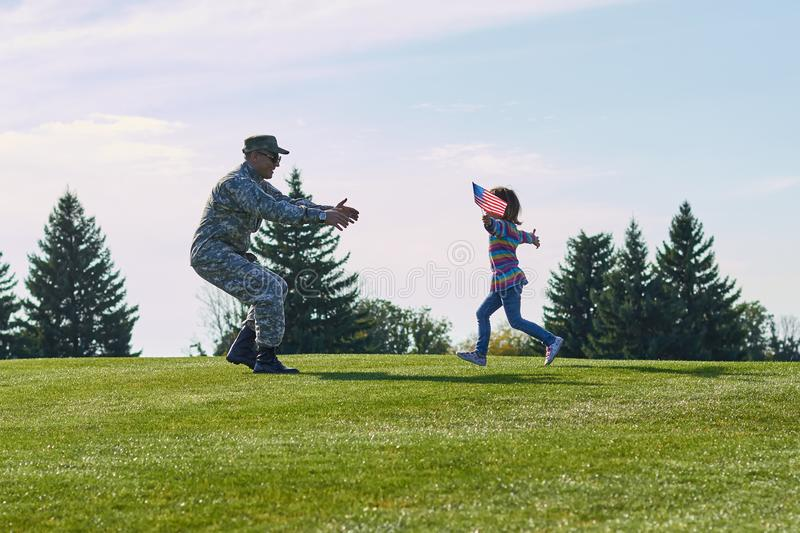 Girl running to her military father, side view. stock photography