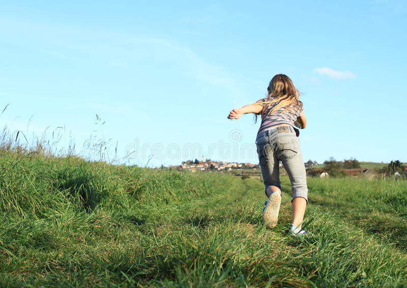 Girl running to village. Girl - kid with long running on a meadow to a village on hill royalty free stock photo