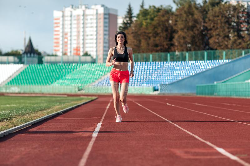 Girl running track on stadium. Real front view of young woman in pink shorts and tank top and pink sneakers. Outdoors, sport.  stock photos
