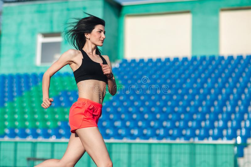 Girl running track on stadium. Real side view of young brunette woman in pink shorts and tank top and pink sneakers. Outdoors,. Girl running track on stadium royalty free stock images