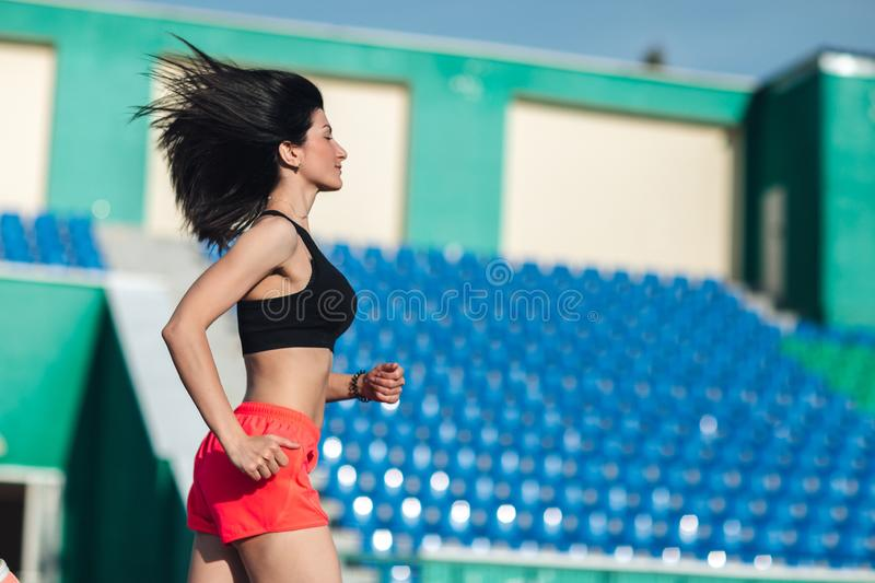 Girl running track on stadium. Real side view of young brunette woman in pink shorts and tank top and pink sneakers. Outdoors,. Girl running track on stadium royalty free stock photo
