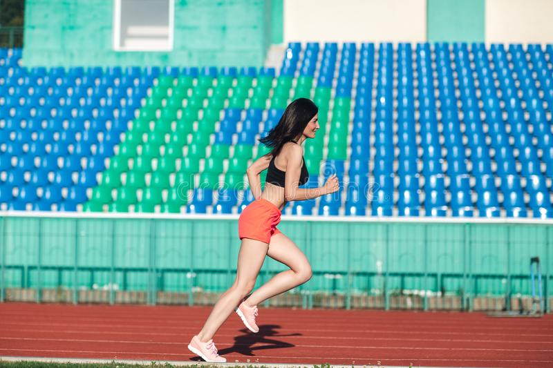 Girl running track on stadium. Real side view of young woman in pink shorts and tank top and pink sneakers. Outdoors, sport.  royalty free stock photo