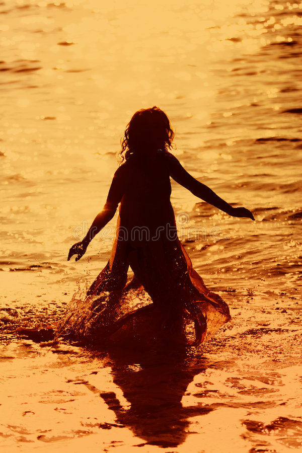 Girl running in the water royalty free stock image
