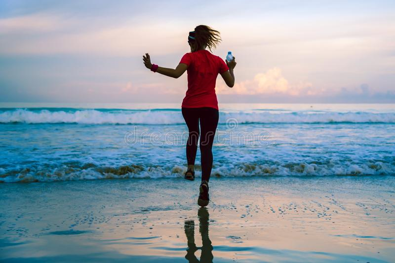 Girl running workout jogging on the beach in the morning. relax and happy with running on the sea. in summer. Girl relax Jogging exercise on the beach royalty free stock photography
