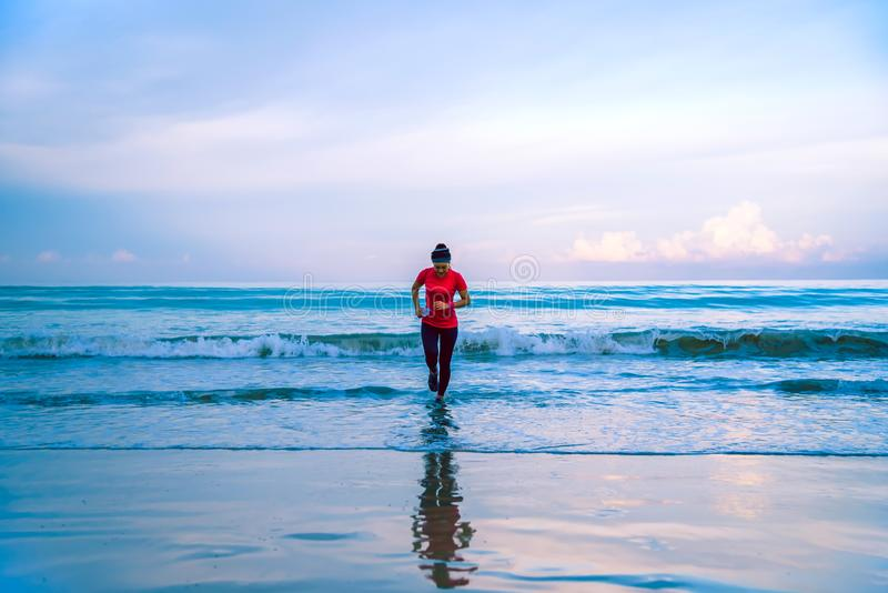 Girl running workout jogging on the beach in the morning. relax and happy with running on the sea. in summer. Girl running workout jogging on the beach in the stock photo