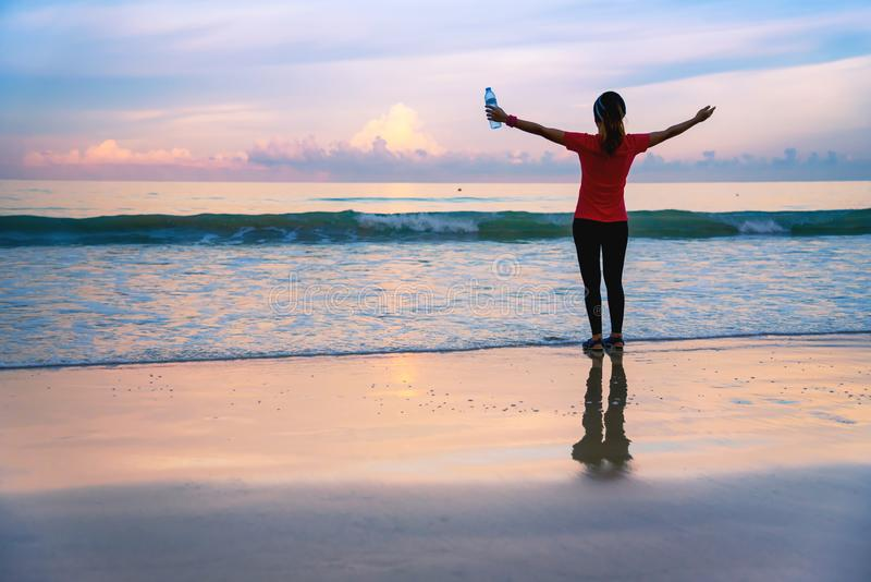 Girl running workout jogging on the beach in the morning. relax and happy with running on the sea. in summer. Girl running workout jogging on the beach in the stock images