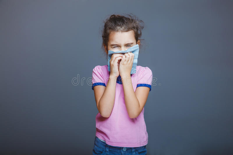 Girl with a runny nose pressed handkerchief to her. Girl with a runny nose pressed her handkerchief to her nose royalty free stock photography