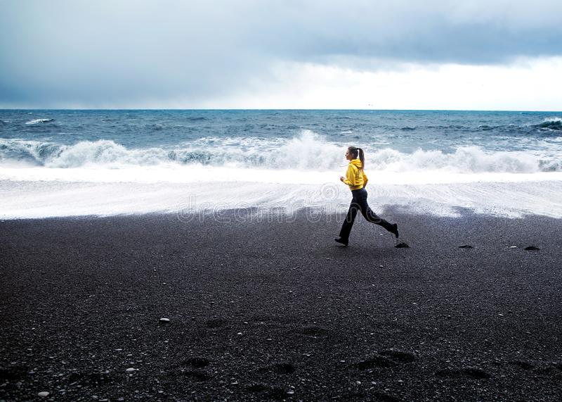 Girl runs along the beach near the Atlantic Ocean in Iceland stock image