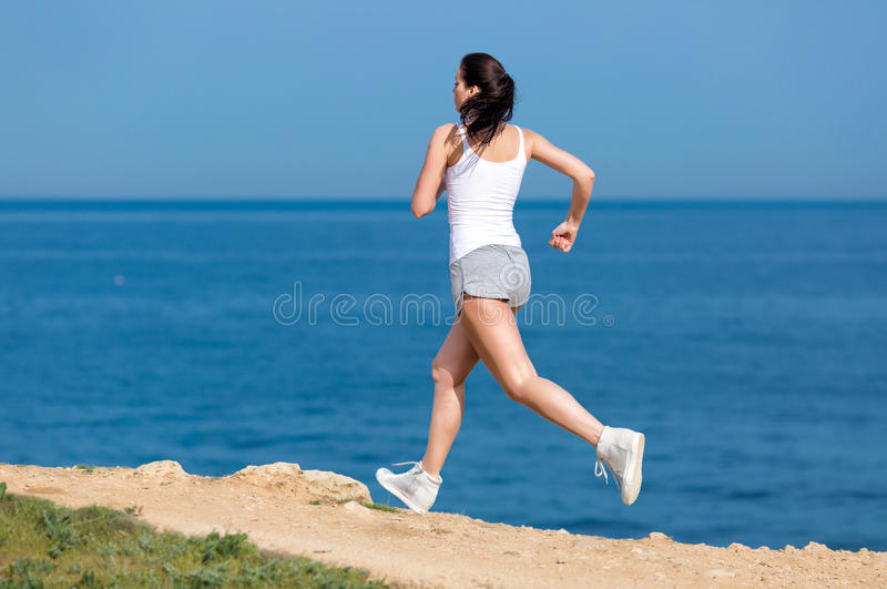 Girl runs along seashore. Jogging. Woman in white tank top and gray sports briefs runs along seashore royalty free stock images