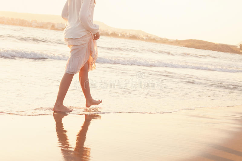 The Girl Runs Barefoot along the Sandy Beach of the Sea stock image