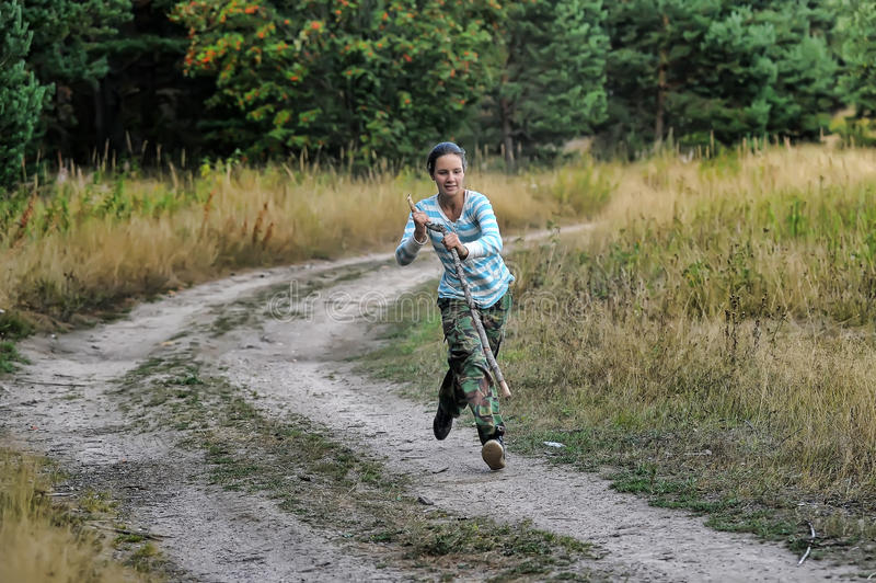 Girl runs and jumps with a cane stock photo