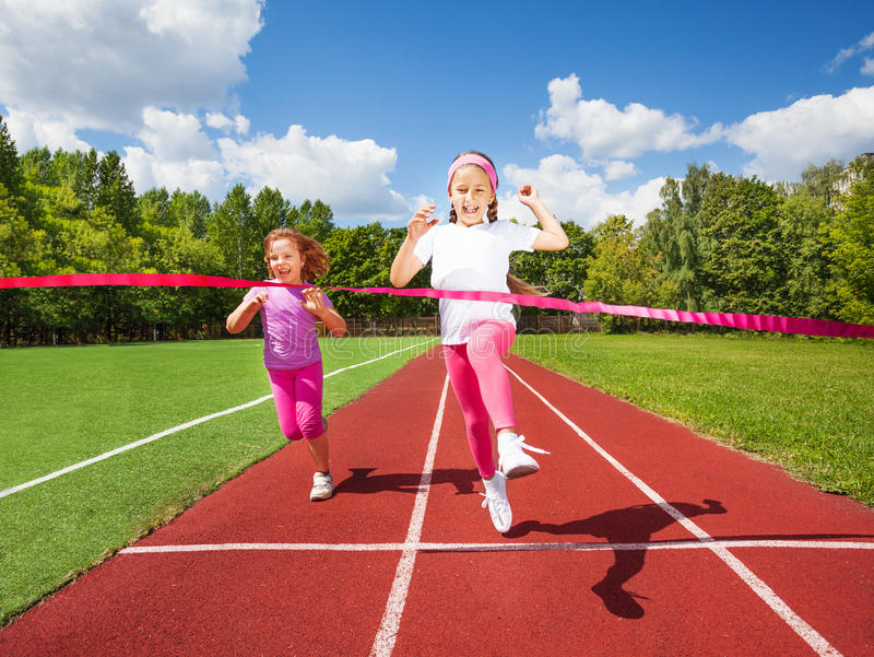 Girl runs and reaches ribbon excited to win stock image