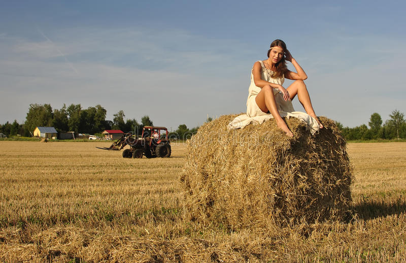 Girl in a rural clothing sitting on the haystack