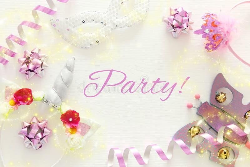 girl& x27; s党概念 独角兽顶头装饰、桃红色鞭子、面具和玩具在白色木背景 图库摄影
