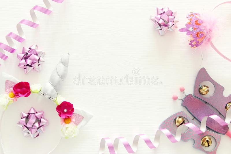 girl& x27; s党概念 独角兽顶头装饰、桃红色鞭子和玩具在白色木背景 库存照片