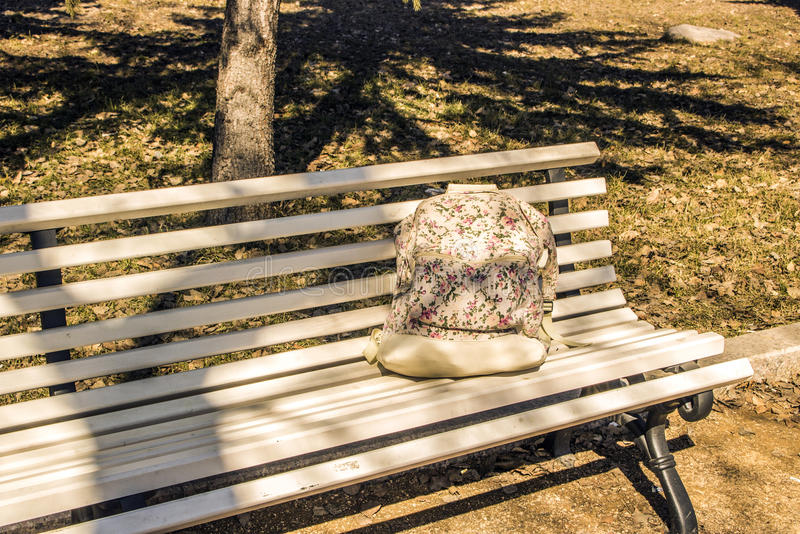 The girl backpack on a bench in the park royalty free stock photo
