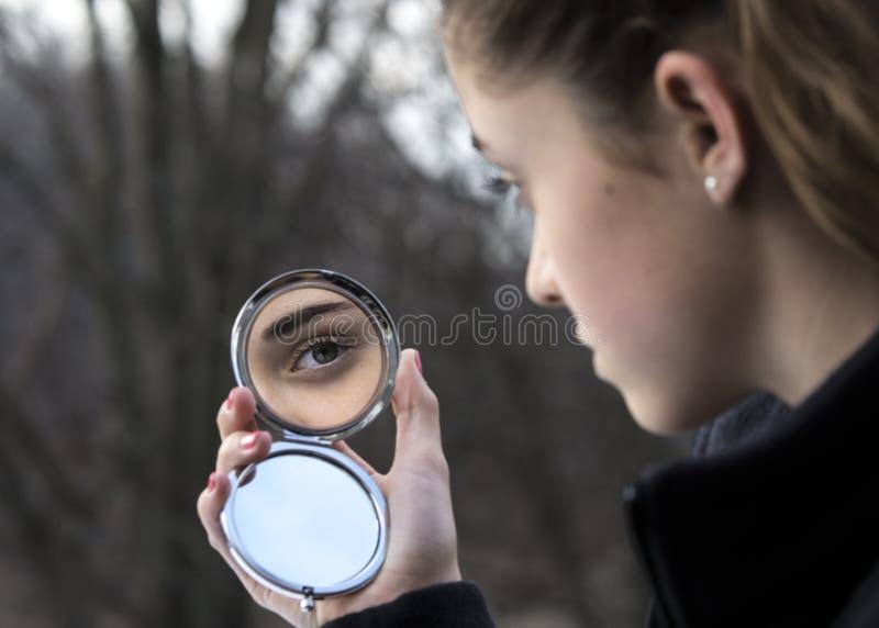Girl's eye in compact mirror stock photo