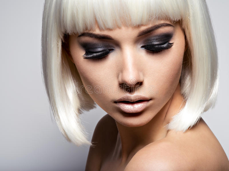 The girl's face closeup with long black lashes. fashion makeup royalty free stock photos