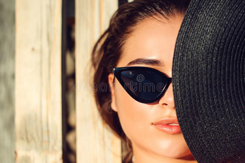 The girl`s half face is covered by black hat. Sensual lips, perfect skin. Model wears trendy sunglasses. Woman sunbathing on a stock image
