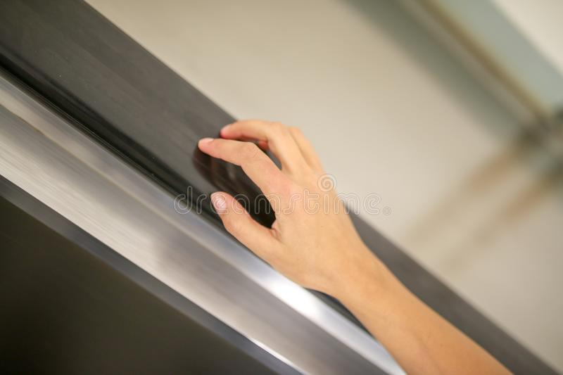 The girl`s hand on the escalator in the metro royalty free stock photography