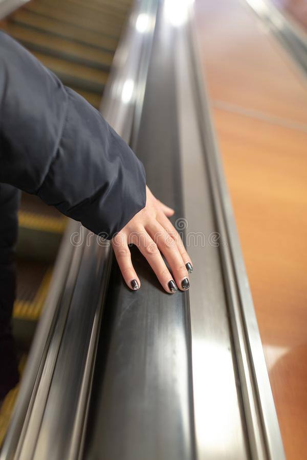 Girl`s hand on the escalator in the subway royalty free stock images