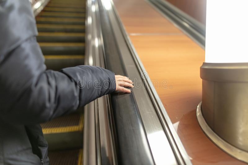 Girl`s hand on the escalator in the subway royalty free stock photo