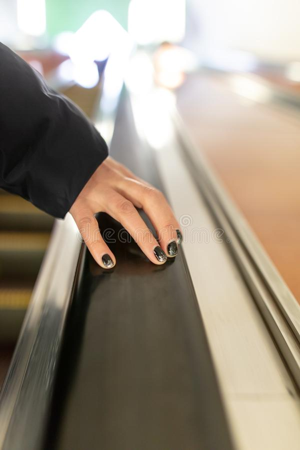Girl`s hand on the escalator in the subway stock images