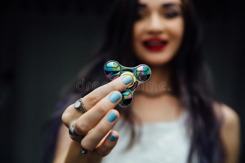 Girl`s hand with fidget spinner. Holds a shiny metallic hand spinner. Hippies and Bohemia. Girl`s hand with fidget spinner. Holds a shiny metallic hand spinner royalty free stock photo