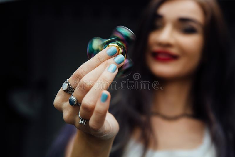 Girl`s hand with fidget spinner. Holds a shiny metallic hand spinner. Hippies and Bohemia. Girl`s hand with fidget spinner. Holds a shiny metallic hand spinner stock photo