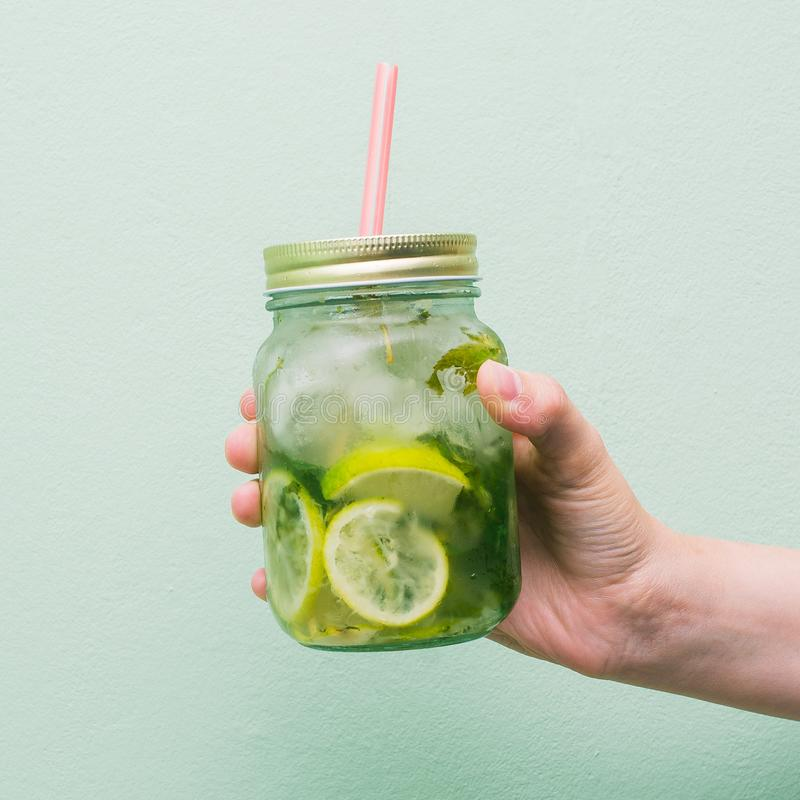 A girl`s hand is holding a jar of fruit drink. Non-alcoholic fresh cocktail in a glass goblet with a pink tube. Summer refreshing. A girl`s hand is holding a jar stock photography