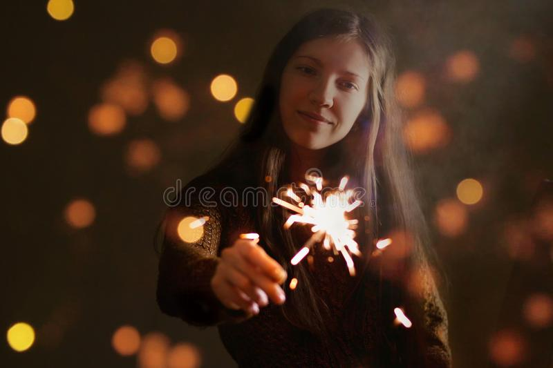 Girl`s hand holding a sparkler. In the dark. Night. Isolated on. A black background stock photos