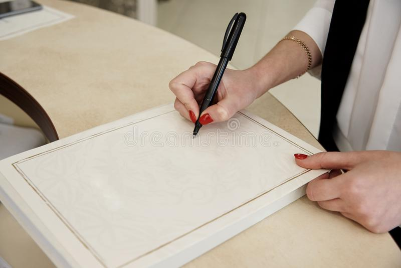 The girl`s hand holds a pen on sheet of paper. stock photography