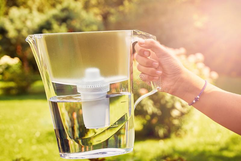 Girl`s hand holds a water filter jug illuminated by sun rays in a sunny summer garden in a warm day stock photos