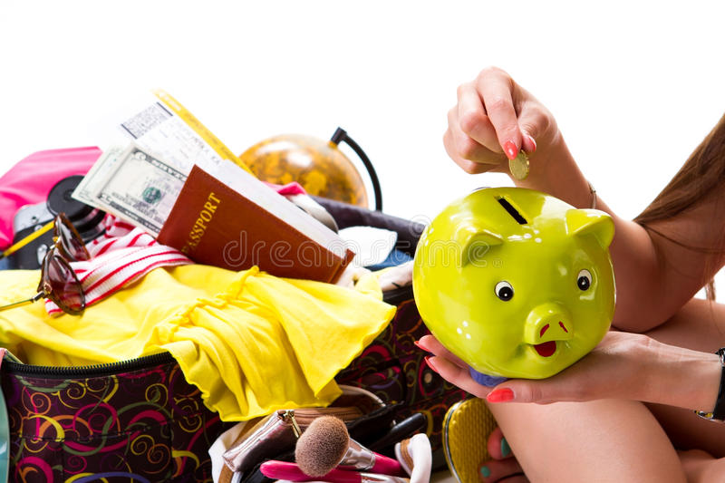 Girl's hand with piggy bank. Passport on filled suitcase. Savings for next holiday season. Make your dreams come true royalty free stock image