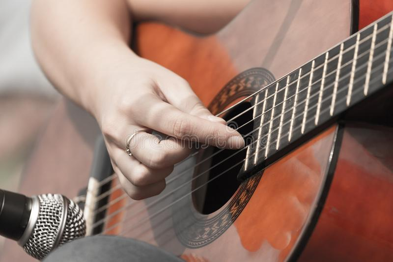 Girl`s hand playing guitar royalty free stock image