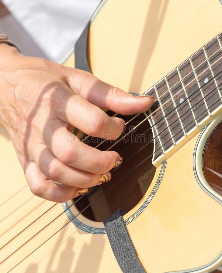 Girl`s hand playing guitar stock photography