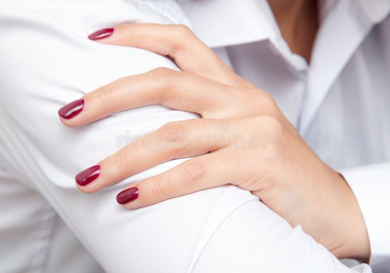 Girl`s hand with red manicure on a white shirt stock photography