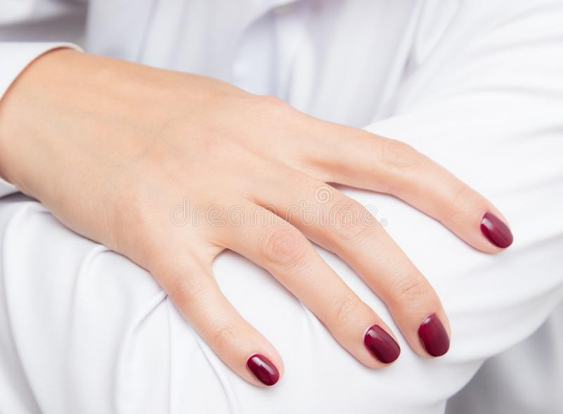 Girl`s hand with red manicure on a white shirt royalty free stock photos